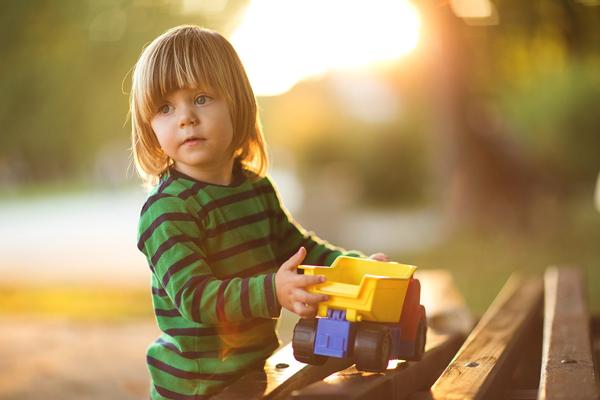 boy playing with his truck in the park