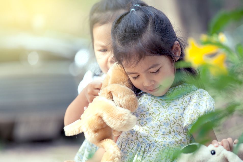 young girl with plush bear toys