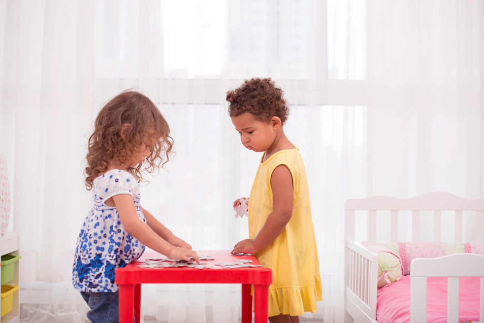 two girls playing with jigsaw puzzle