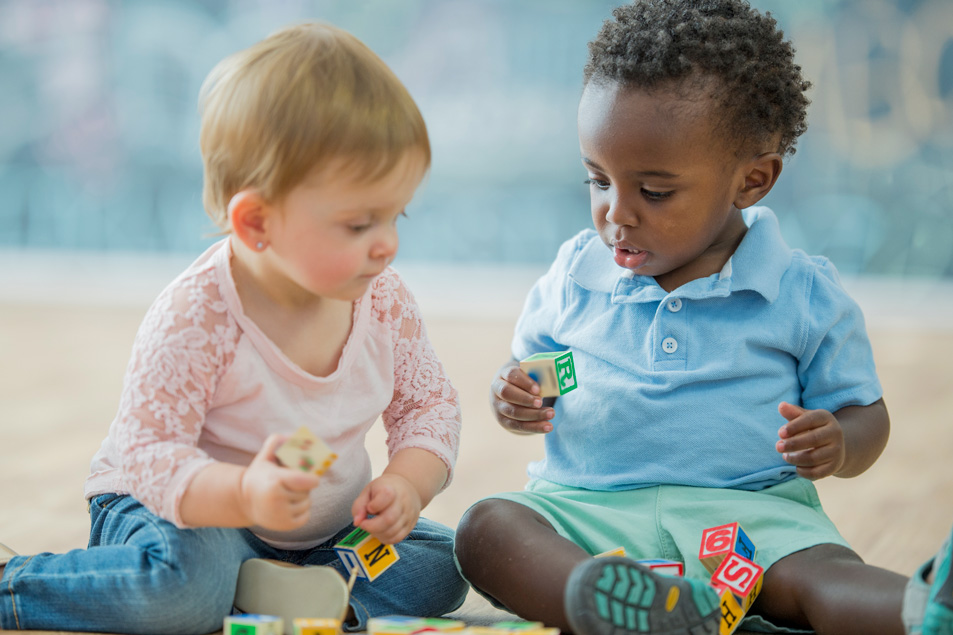 two toddlers playing with wooden letter blocks