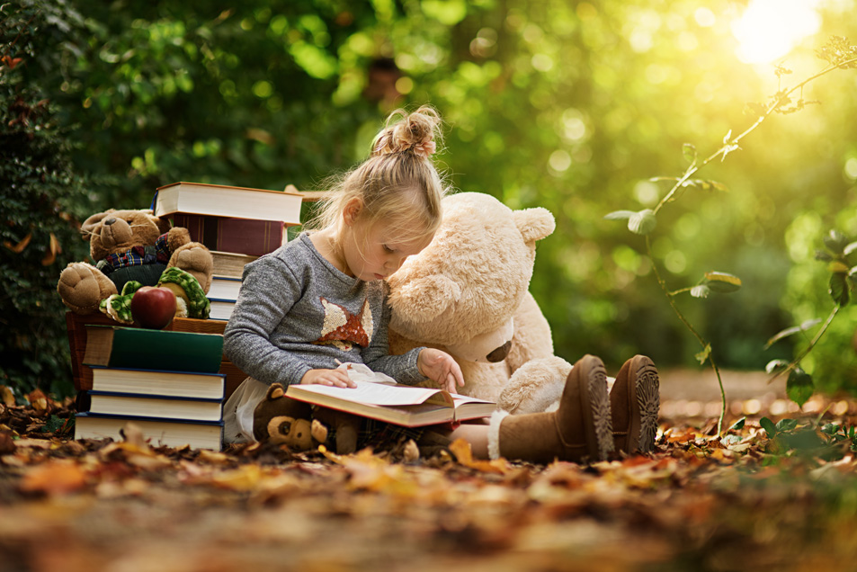 little girl with book in park