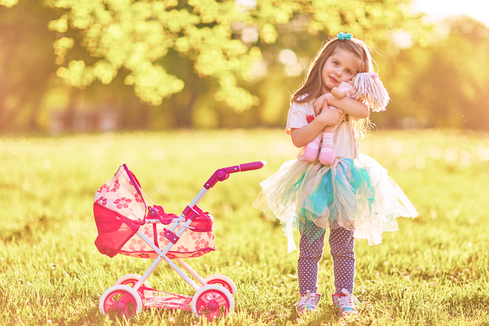 girl playing with doll stroller